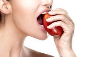 Closeup of beautiful and healthy mouth biting a red apple. Closeup portrait isolated on white background