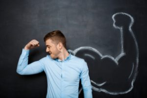 Picture of funny suited business man with fake muscle arms over blackboard. hand whrite