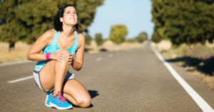 Woman crying for a painful knee injury during running training.